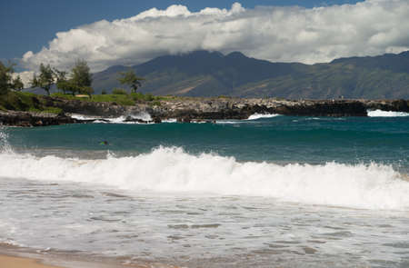 Crashing waves and scenic island views at DT Fleming Beach Park on the beautiful Hawaiian island of Maui photo