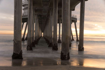 Long exposure captures slow moving waves under The Huntington Beah Pier in Huntington Beach, California
