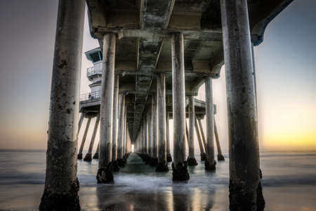 Long exposure captures slow moving waves under The Huntington Beah Pier in Huntington Beach, California photo