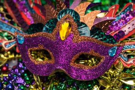 Close up view of purple sequined Mardi Gras mask with colorful beads out of focus in the background photo