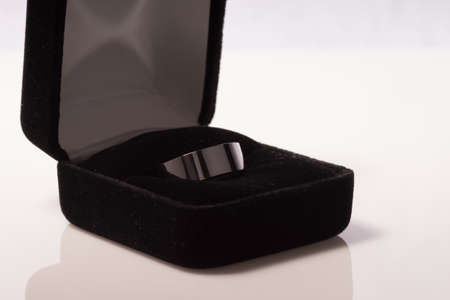 Simple mens tungsten wedding ring in gift box. Isolated on white background with slight reflection