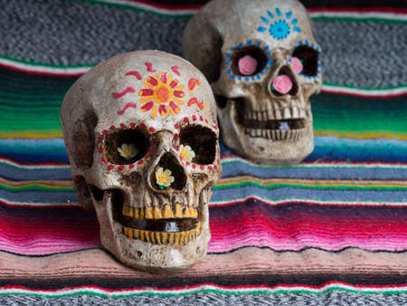 Day of the Dead (dia de los muertos) decorated skulls with colorful Mexican blanket