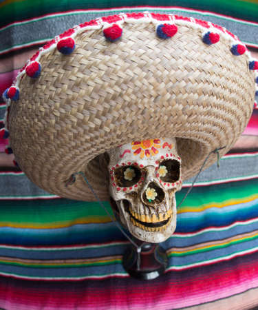 Decorated Dia De Los Muertos Skull wearing sombrero with colorful Mexican blanket in the background. Stock Photo