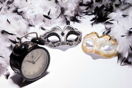 Time to celebrate. Alarm clock with Mardi Gras mask and feather boa