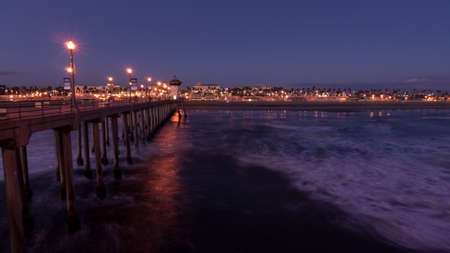 City lights and slow moving waves under the Huntington Beach Pier at twilight photo