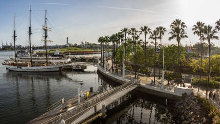 long: Boats docked and people in motion at Rainbow Harbor in Long Beach, California
