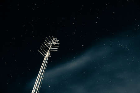 Looking up at an antenna with a partly cloudy starry night Stok Fotoğraf