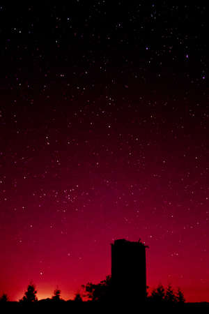 Rural view of a starry night with magenta toning with silhouetted silo Stok Fotoğraf
