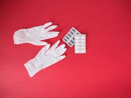 Close up of vitamin pills and white latex glove. One of the ways to reduce the spread of virus. Prevention the spread of COVID-19.