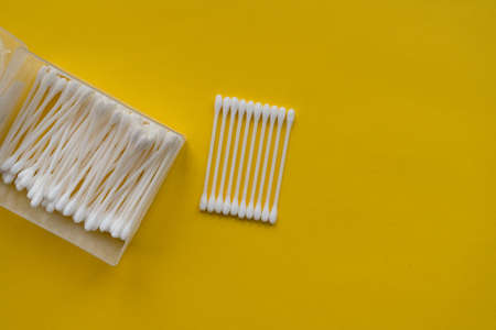 Flat lay composition with cotton swabs on yellow background. Top view
