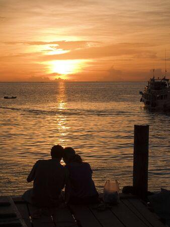 picknick: A couple cuddling on a dock Koh Tao Thailand Stock Photo