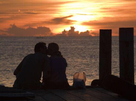 A couple kissing on a dock on Koh Tao Thailand photo