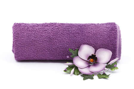 pebles: Purple towel and flower as a spa decoration isolated on white background Stock Photo