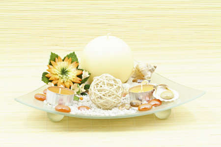Home decoration with candle and artificial flower on decorative glass plate photo