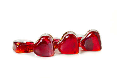 Red heart shaped gems on white background photo