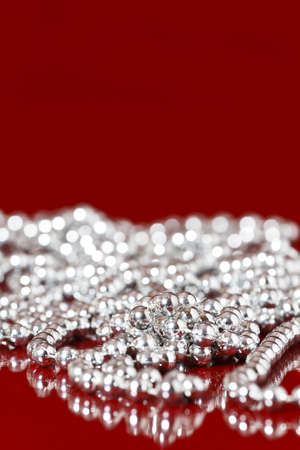 Shiny Silver Pearls on red background photo
