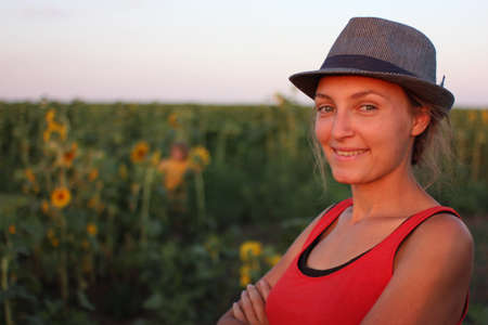 Beautiful girl portrait at the summer sunset soft and warm lights in the field of sunflowers.