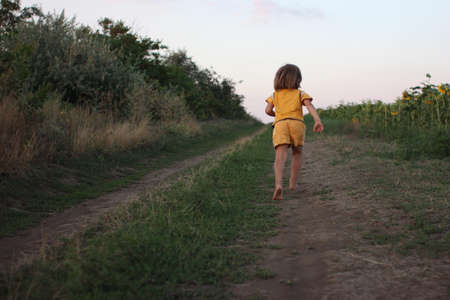 Little boy running barefoot by the road near the field at the summer afternoon light.