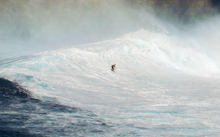 MAUI, HAWAII, USA - DECEMBER 15, 2013: Unknown surfer is riding a big wave at Jaws Editorial