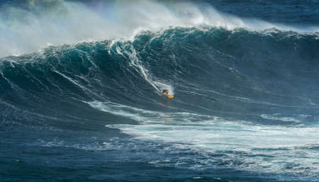 wave: MAUI, HAWAII, USA - DECEMBER 15, 2013: Unknown surfer is riding a big wave at Jaws Editorial