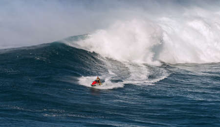 jetski: MAUI, HAWAII, USA - DECEMBER 15, 2013: jetski driver brings a surfer away from the next breaking wave