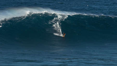 granola: MAUI, HAWAII, USA - DECEMBER 15, 2013: Unknown surfer is riding a big wave at Jaws Editorial