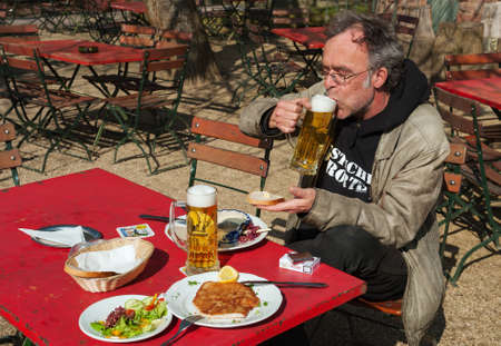ERFELDEN, HESSEN, GERMANY-MARCH 15, 2012: Tired hiker enjoys his beer and his meal