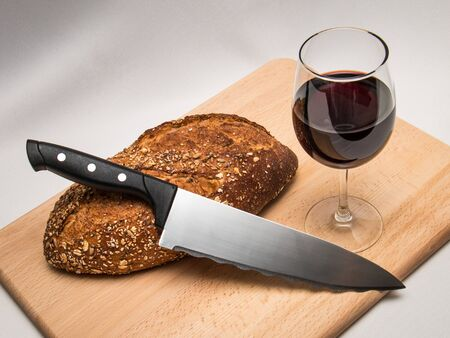 Traditional Christian Communion elements of bread and wine on a cutting board with a knife