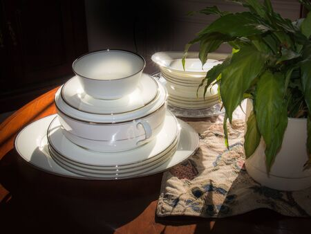 Stacks of formal china dishes on a cherry table in slanting dawn sunlight with a plant and placemat Archivio Fotografico - 142280793