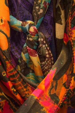 Closeup of several women's scarves hanging in a closet