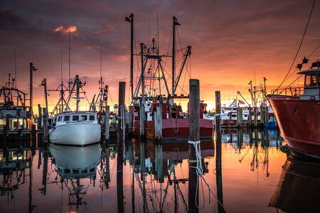Wide shot of the fishing fleet at Viking Village while a wonderful sunrise unfolds Imagens