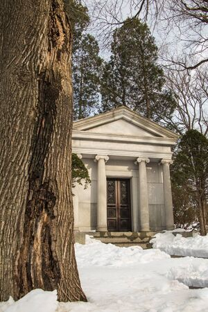 A mausoleum next to a large tree in winter at a cemetery in Reading, PA