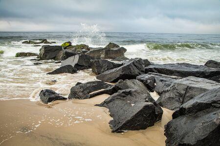 Seashore scene with waves crashing on a rock jetty under a cloudy blue sky Banco de Imagens