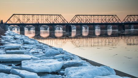 Sunrise in Harrisburg, PA with a railroad bridge over the Susquehanna and a walkway filled with ice remnants