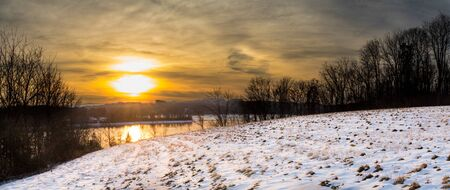 Panoramic landscape of Blue Marsh Lake in Berks County, PA in winter with a snow-covered field in the foreground
