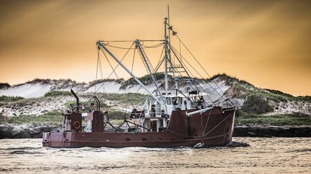 A workboat heads out of Barnegat Inlet in the morning light