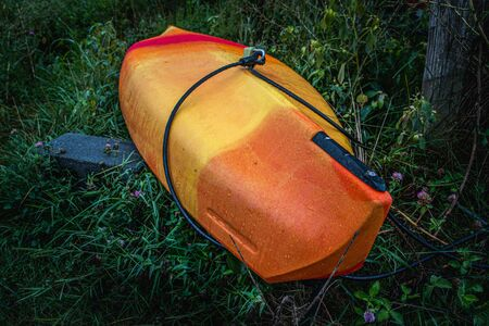 An orange and tellow kayak rests in a meadow next to Speedwell Forge Lake Stock fotó