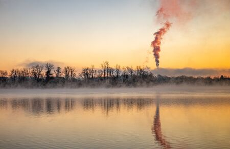 Dawn at Lake Ontelaunee with a tree line and mysterious cloud plume over water