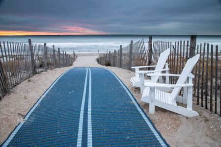 A walking mat, pair of beach chairs and twin dune fences line the way to an empty beach on a cloudy dawn