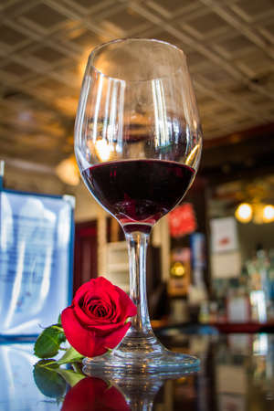 Low angle shot of a half-full wine glass sitting on a bar with a single red rose at its base Foto de archivo