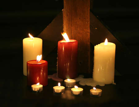 Candles set against a rough wood beam in the darkness Imagens