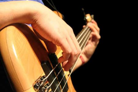 A bass guitar player plucks the strings Reklamní fotografie
