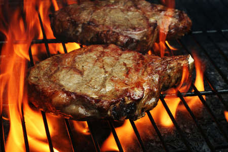 sizzle: Two Juicy stakes grilling on the barbeque with lots of flame licking around them Stock Photo