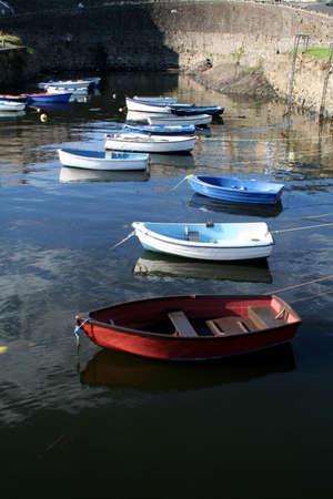 手漕ぎボート釣りに行くを待っている港に座っています。