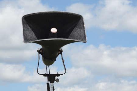 A loud speaker set up in a camp against a blue sky photo
