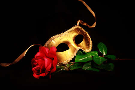 resting mask: A golden mask resting on a rose Stock Photo