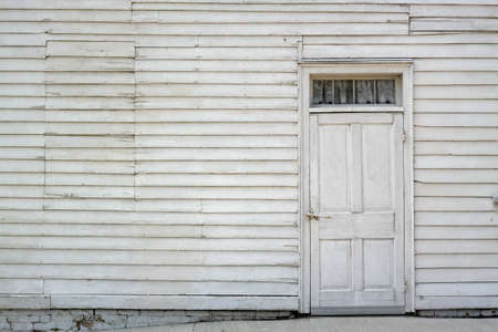 Whitewashed door on a white wall with window boarded up