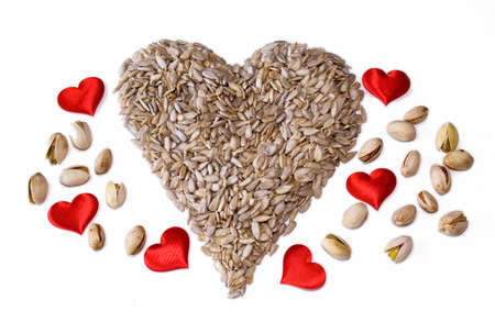 A healthy heart made from sunflower seeds  Shelled  with Pistachios and red hearts Imagens