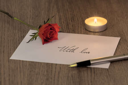 A love letter reading With love with a rose, a candle and a pen on top. photo