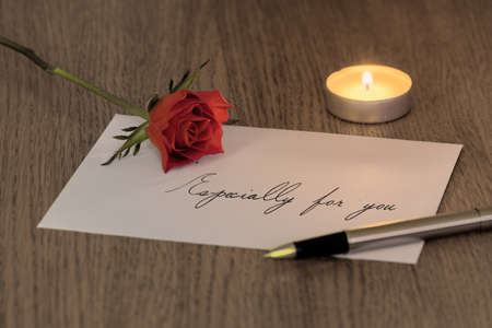 A love letter reading Especially for you with a rose, a candle and a pen on top. photo